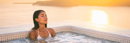 Luxury wellness spa jacuzzi pool Asian woman relaxing in swimming hot tub at outdoor hotel terrace. Banner panorama of young lady enjoying hydrotherapy massage water jets. Stock Photo - 108085346