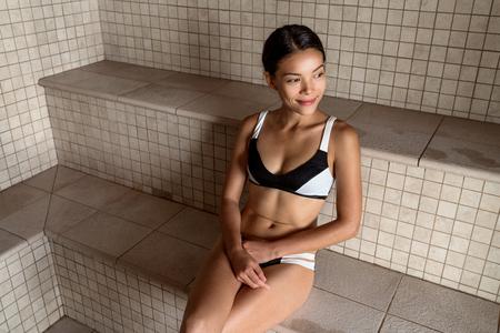 Steam room woman relaxing in wellness spa resort taking a steam bath in wet sauna. Asian girl enjoying heat. Stock Photo