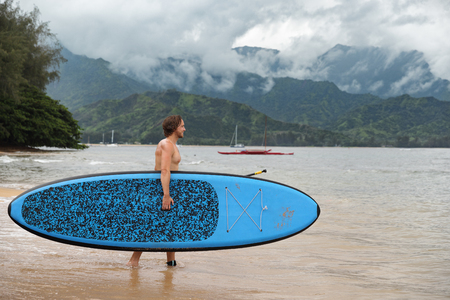 Stand up paddleboard fit man carrying paddle board going on ocean swim watersport activity at Puu Poa beach, Hanalei Bay, Kauai, Hawaii, USA. Hawaii travel sport athlete.