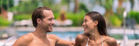 Happy couple having talking at luxury resort hotel travel beach holiday together on summer vacation. Asian woman, man relaxing by swimming pool