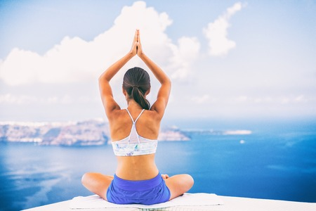 Woman doing yoga meditation in morning sunshine nature landscape- relaxing in beach background. Imagens