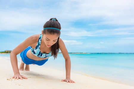 Exercise fitness push up training girl doing bodyweight workout on beach. Asian woman fit active sport lifestyle.