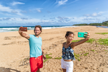 Self absorbed young people taking selfie pictures of themselves on beach vacation. Social media addiction, two friends holding smart phones, funny concept.