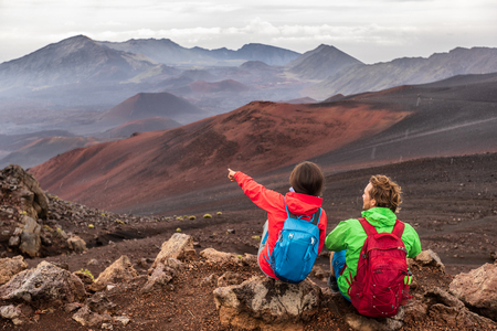 Hiking travel vacation in Maui volcano, Hawaii. USA travel woman with backpack pointing at Haleakala volcano landscape. Couple tourists resting outdoors. 스톡 콘텐츠