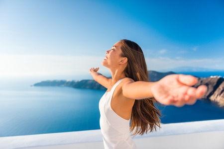 Europe cruise destination Santorini Greece travel vacation carefree woman enjoying freedom with open arms in famous travel holiday. Elegant Asian girl on greek travel luxury resort in Oia Santorini.