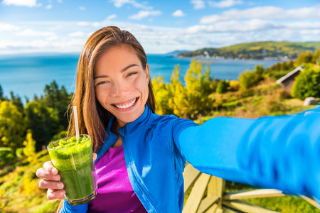 Healthy green smoothie juice drinking selfie girl taking picture clean food diet healthy nutrition. Asian woman eating fresh spinach vegetable juicing in beautiful outdoors autumn nature. Stock Photo