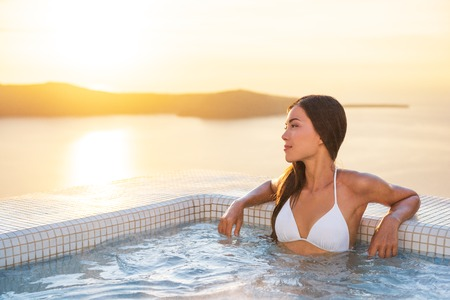 Luxury hotel travel woman in spa pool hotel with Mediterranean sea background. Santorini vacation summer holidays girl enjoying holiday getaway. Asian model relaxing. 版權商用圖片
