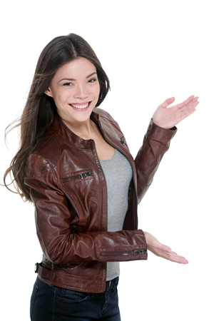 Casual attractive woman presenting blank copy space something on the side with open hands showing copyspace on white background. Asian model cut-out in leather jacket.