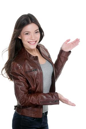 Toevallige aantrekkelijke vrouw die lege exemplaarruimte voorstellen iets aan de kant met open handen die copyspace op witte achtergrond tonen. Aziatisch model uitgesneden in leren jas. Stockfoto