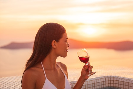 Luxury vacation woman drinking red wine glass in private jacuzzi at luxury hotel destination. Santorini europe getaway Asian girl relaxing in bikini swimming in pool.