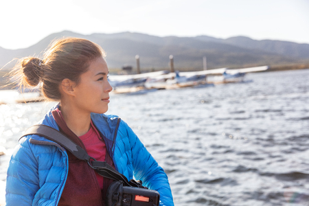 Tourist woman on adventure travel outdoors vacation in Alaska. Asian girl photographer on cruise excursion with floatplanes in the background. Stock Photo