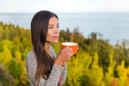 Nature outdoors coffee drinking woman relaxing in forest autumn sunshine enjoying her morning coffee. Happy multiracial canadian Asian Chinese  Caucasian girl in her 20s, Canada.