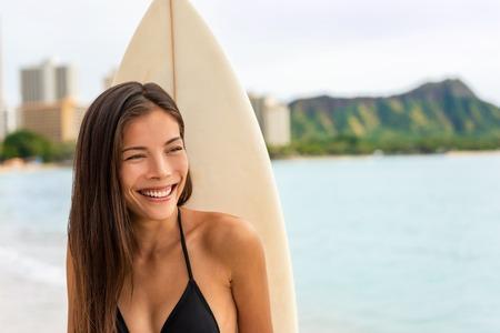 Asian surfer girl smiling portrait. Beautiful surfing woman with surfboard on Waikiki beach, Hawaii, USA travel surf lifestyle.