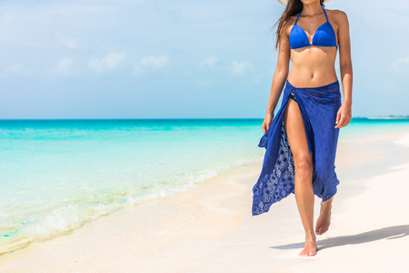 Woman walking on beach in blue fashion beachwear bathing suit and sarong pareo sun skirt relaxing in luxury Caribbean vacation holidays. Summer or winter getaway destination.