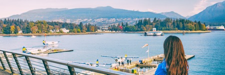Woman walking in Coal Harbour in Vancouver city in fall, BC, Canada. Autumn travel lifestyle panorama banner.