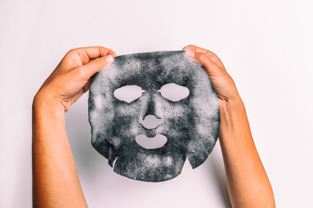 Bubble mask woman doing facial beauty treatment with charcoal detox purifying pores product holding product against white background.