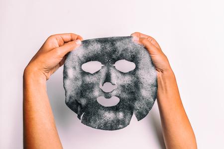 Mujer de máscara de burbuja haciendo tratamiento de belleza facial con desintoxicación de carbón purificante producto de poros con producto sobre fondo blanco