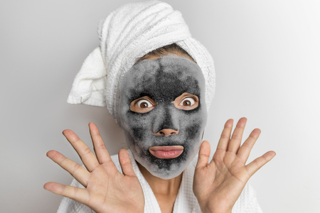 Face mask bubble foam facial funny woman at beauty spa looking shocked or surprised, scary chemicals in beauty products. Asian girl wearing bath towel on hair. Standard-Bild - 110811434