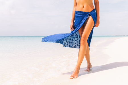 Caribbean vacation travel - woman leg closeup walking on white sand relaxing in beach cover-up pareo beachwear. Sexy lean and tanned legs. Sunmmer holidays, weight loss or epilation concept. 스톡 콘텐츠