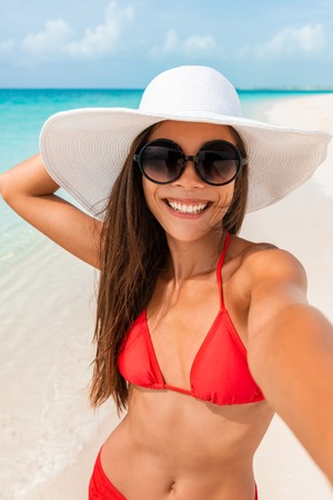 Happy girl taking selfie in summer beach vacation smiling of fun on tropical Caribbean holidays. Asian woman holding camera phone taking picture outside. Stock Photo