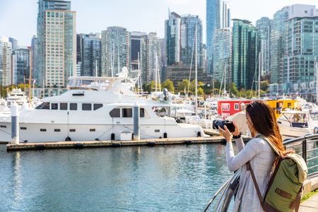 Vancouver Canada tourist woman taking picture with camera at Coal Harbour on summer holidays in canadian city. Urban lifestyle.