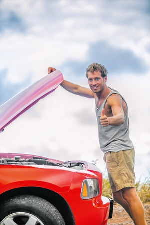 Car maintenance mechanic checking engine with open hood on road trip - happy customer man doing thumbs up for good inspection of motor on sports automobile. Roadside repair help assistance. Stock Photo