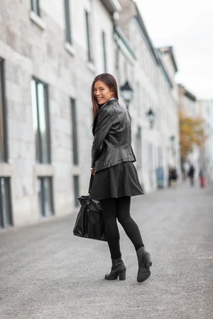 Fashion young woman walking on city street commute to work. Urban lifestyle people in leather jacket in full length in autumn fall. Trendy modern female. Multiracial Asian Caucasian model.