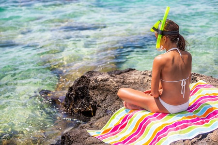 Young woman relaxing on beach after snorkel fun sport activity in ocean water, snorkeling in Hawaii. Marine life in coral reefs, girl in bikini enjoying holidays.