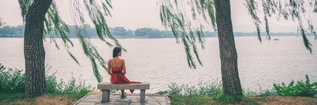 Nature banner woman sitting on park bench relaxing at lake view of Summer Palace in Beijing, China. Asia travel. Romantic scenery of lady in red dress under weeping willow trees in serenity. Stock Photo