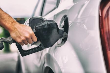 Car pumping gas at gas pump. Closeup of man pumping gasoline fuel in car at gas station. Stockfoto