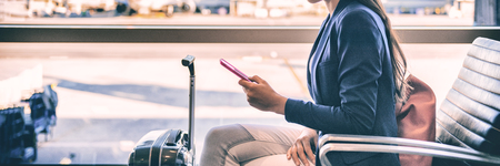 Plane passenger woman waiting for flight departure texting sms message on mobile phone at lounge airport. Businesspeople travel lifestyle panoramic banner. 免版税图像 - 110812213