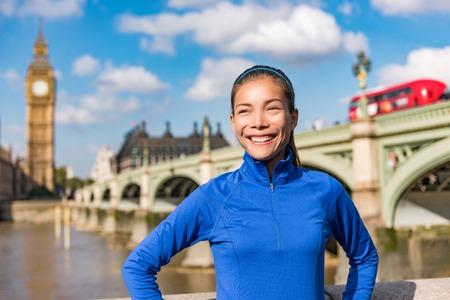 London city healthy active fitness woman running near Big Ben. Female runner girl jogging training. Asian athlete smiling happy on Westminster Bridge, London, England, United Kingdom.
