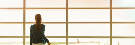 Airport travel businesswoman on business trip vacation waiting for flight looking out the window at tarmac. Banner panoramic header with copy space on windows background. People traveling lifestyle. Stock Photo