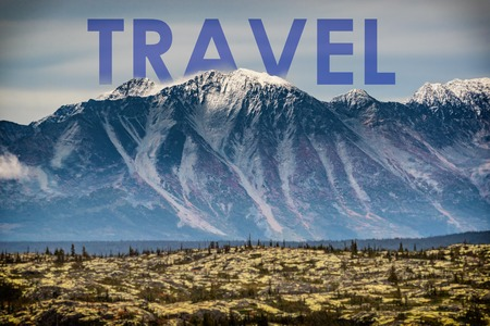 TRAVEL written in capital as title above landscape of mountains with snow capped peaks - inspirational quote on nature background. Adventure around the world outside. Alaska. USA.