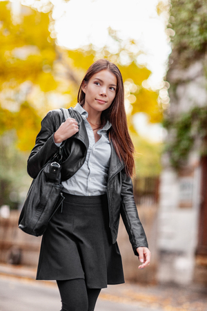Young woman walking in city street, autumn lifestyle wearing fashion outfit clothing. urban professional girl in black leather jacket, leggings, skirt, boots. Trendy modern multiracial Asian model.