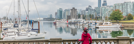 Vancouver woman at city skyline wearing helmet biking in harbour front of urban background panorama banner.