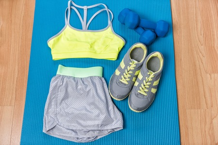 Fitness outfit on exercise mat with weights and running shoes. Sports bra and grey shorts for training at home . Style and fashion activewear. Stock Photo