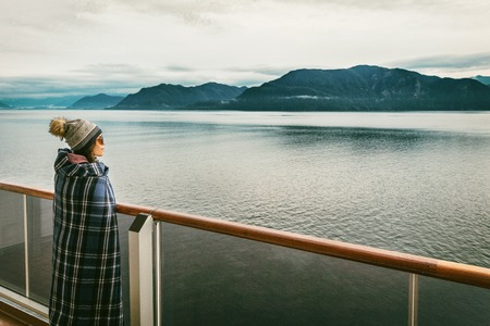 Alaska cruise travel luxury vacation woman watching inside passage scenic cruising day on balcony deck enjoying view of mountains and nature landscape. Asian girl tourist with wool blanket. Stok Fotoğraf