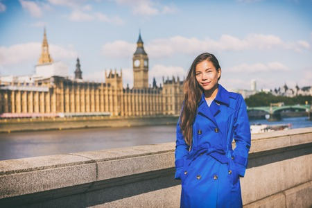 London woman european city traveler in blue trench coat outerwear at famous UK travel destination, Westminster Big Ben on Thames river. Europe holiday Asian businesswoman happy in Autumn vacation.