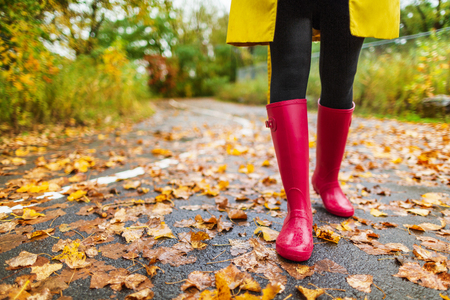 Autumn fall city lifestyle colorful leaves and red rain boots woman feet walking in park outside.