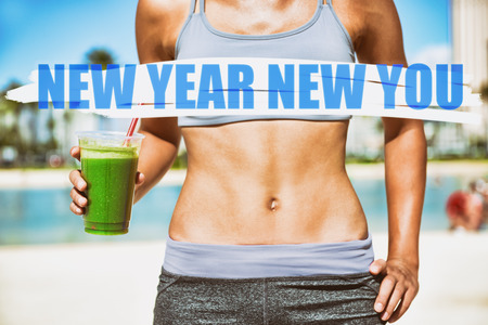New Year resolution for 2019 : Getting in shape with fitness and diet. Fit woman with abs flat stomach eating drinking green smoothie. Stock Photo - 114551193