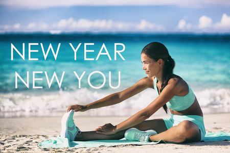 New Year new you motivational quote message on beach background. Asian woman training stretching on yoga mat for fitness resolution goal.