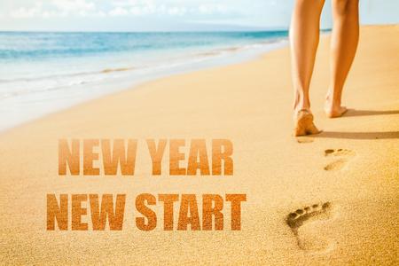 Nieuwjaar 2019 Nieuwe start resolutie concept. De benen van de strandvrouw lopen blootsvoets op zand en laten voetafdrukken achter in de zonsondergang. Vakantie reizen vrijheid mensen.