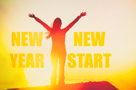 New Year New Start success winner concept happy woman motivation inspirational quote on silhouette person in sunset with arms up in confidence. You can start to change your life.
