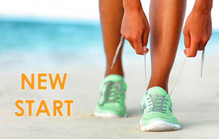 New Start fitness new year resolution runner woman tying up laces of running shoes getting ready to run for weight loss.