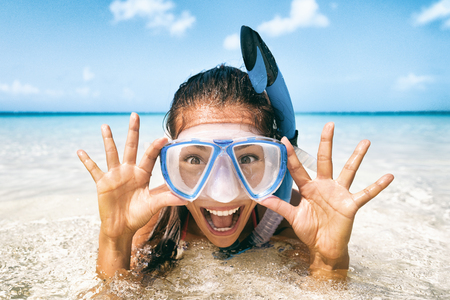 Snorkel fun woman Beach vacation tourist Asian girl swimming in scuba mask making a goofy face. Closeup portrait of Asian girl on her travel holidays. Summer or winter Caribbean destination. Stock Photo