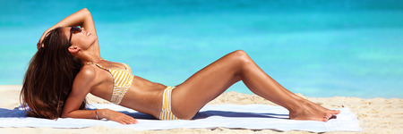 Suntan bikini woman sun tanning on beach - Asian sexy body model lying down on beach towel on perfect blue ocean water background banner panorama. Imagens