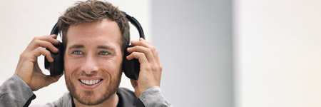 Music headphones man listening to audiobook online or songs on phone app. Happy smiling young person wearing wireless earphones. Home lifestyle banner panorama. Stock Photo