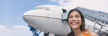 Airport travel Asian woman tourist happy boarding plane or on arrival walking on tarmac. Airplane passenger smiling at departure. Banner panorama background.