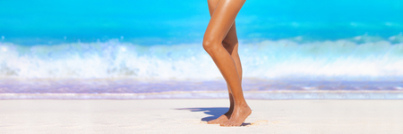 Smooth sun tanned slim legs standing walking on beach ocean banner header- Beauty spa salon background for waxing depilation laser treatment skincare for women. Stock Photo